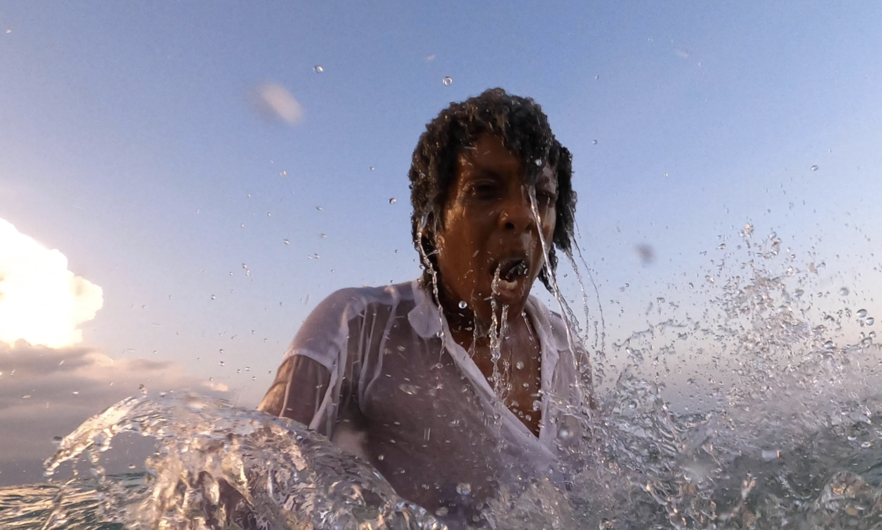 A woman in a white shirt emerges from the water