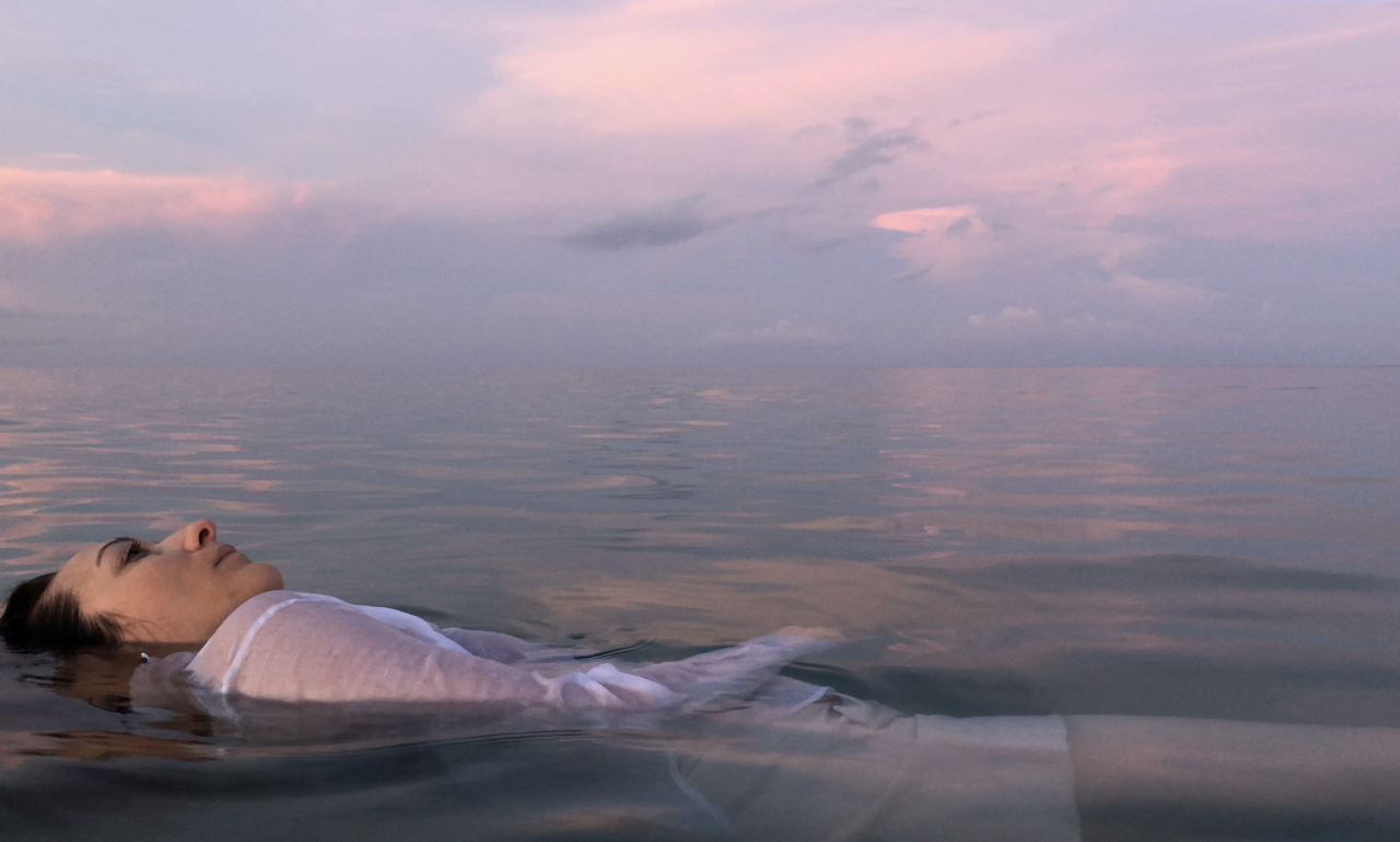 A woman in white fabric lays in a body of water reflecting the sunset